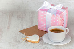 Gift box wrapped in pink dotted paper, heart shaped love cookie, a cup of coffee and an empty kraft card over a white wood backgro Royalty Free Stock Photos