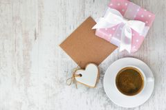 Gift box wrapped in pink dotted paper, heart shaped love cookie, a cup of coffee and an empty kraft card over a white wood backgro Royalty Free Stock Images