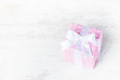 Gift box wrapped in pink dotted paper and tied satin bow over a white wood background. Royalty Free Stock Image