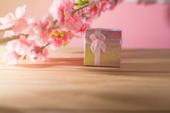 Gift box wrapped and plum blossom Christmas and Newyear presents with bows and ribbons, Christmas frame boxing day background. Gift box wrapped and plum blossom Stock Image
