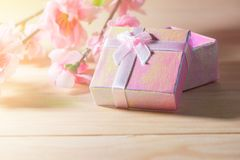 Gift box wrapped and plum blossom Christmas and Newyear presents with bows and ribbons, Christmas frame boxing day background. Gift box wrapped and plum blossom Stock Photos
