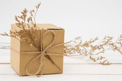Gift box wrapped in recycled paper with grass stock image