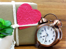 Gift box wrapped in recycled paper with heart and alarm clock Stock Photography