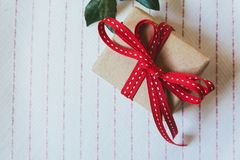 Gift box, wrapped in recycled paper and red bow on on white tablecloth royalty free stock images