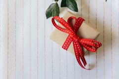 Gift box, wrapped in recycled paper and red bow on on white tablecloth royalty free stock photo
