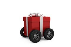 Gift box wrapped in red paper with ribbon on wheels Royalty Free Stock Photos