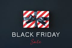 Black friday gift box. Gift box wrapped in red striped paper and tied with black bow on black background. Black friday concept, top view royalty free stock images