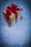 Gift box wrapped in shining golden paper on metallic surface Royalty Free Stock Image