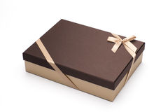 The gift box is wrapped up by a yellow tape with a bow, isolated on white. Stock Photos