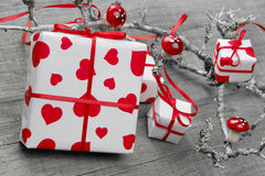 Gift box wrapped in white paper with hearts Stock Image