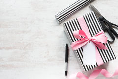 Gift box and wrapping materials on a white wood old background. Greeting note tied over. Stock Photography
