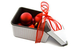 Gift box with xmas balls. Striped gift box filled with xmas balls isolated over white Royalty Free Stock Photos
