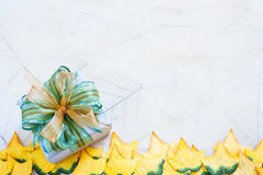 Gift box and yellow leaves Royalty Free Stock Image