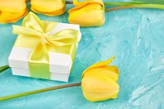 Gift box with yellow ribbon near tulip. White gift box with yellow ribbon near yellow tulip on blue background. Flat lay. Mother or Woman Day. Greeting Card stock images