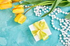 Gift box with yellow ribbon near tulip. White gift box with yellow ribbon near yellow tulip on blue background. Flat lay. Mother or Woman  Day. Greeting Card Royalty Free Stock Images