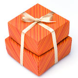 Gift boxes. An orange gift boxes tied with a gold ribbon bow on a white background Stock Photos