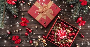 Gift boxes with balls and other holiday items over brown wooden background. Fir tree with baubles, space for text. Top view. Effect snowflakes royalty free stock photos