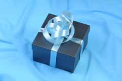 Gift boxes with blue ribbon on silk Royalty Free Stock Photos