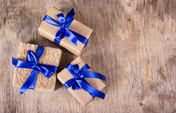 Gift boxes with blue ribbons on the old wooden background. Copy space. Royalty Free Stock Images