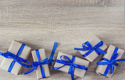 Gift boxes with blue ribbons on a wooden background and empty sp Stock Image