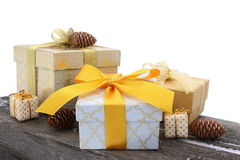 Gift boxes with bows and fir cones on an wooden background i Royalty Free Stock Photos