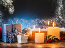 Gift boxes, candle lights and frozen window. Stock Photos