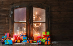 Gift Boxes and Candles at Window on Christmas Royalty Free Stock Photo