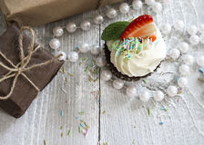 Gift boxes and Chocolate cupcake with white creme and strawberry Stock Images