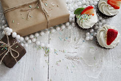 Gift boxes and Chocolate cupcake with white creme and strawberry. On top royalty free stock images