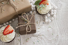 Gift boxes and Chocolate cupcake with white creme and strawberry Stock Image
