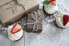 Gift boxes and Chocolate cupcake with white creme and strawberry. On top stock images
