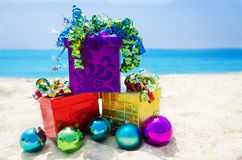 Gift boxes with Christmas balls on the beach - holiday concept Stock Images