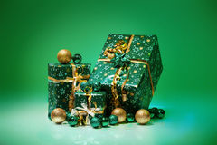 Gift boxes and christmas balls,Isolated on green background Royalty Free Stock Photo
