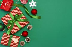 Gift boxes, Christmas balls, toys, fir cones, ribbon on green background. Festive, congratulation, New Year Christmas presents Xma royalty free stock photos