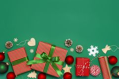 Gift boxes, Christmas balls, toys, fir cones, ribbon on green background. Festive, congratulation, New Year Christmas presents Xma royalty free stock image