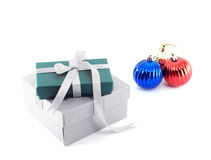 two gift boxes (green and white) with ribbon bow and pile of colorful shiny christmas balls isolated on white background Stock Photos