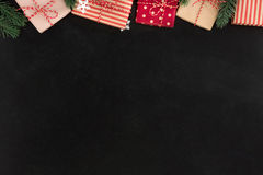 Gift boxes and Christmas ornaments, border design, on blackboard Royalty Free Stock Photo