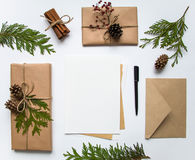 Gift boxes in craft paper and a letter on white background. Christmas or other holiday concept, top view, flat lay Stock Photo