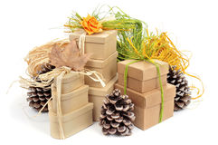 Gift boxes decorated with natural ornaments. Some gift boxes tied with natural raffia of different colors and surrounded by natural ornaments such as pinecones Stock Image