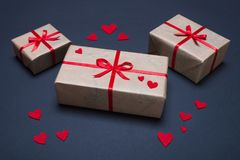 Gift boxes decorated with red ribbons with bows lie on a black background. As well as red hearts lined around boxes Royalty Free Stock Images
