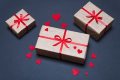 Gift boxes decorated with red ribbons with bows lie on a black background. As well as red hearts lined around boxes Royalty Free Stock Photography