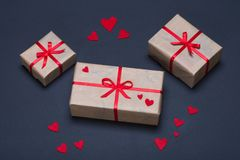 Gift boxes decorated with red ribbons with bows lie on a black background. As well as red hearts lined around boxes Royalty Free Stock Photos