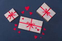 Gift boxes decorated with red ribbons with bows lie on a black background. As well as red hearts lined around boxes Royalty Free Stock Image