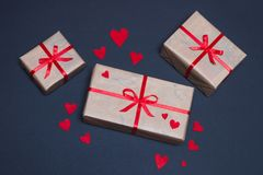 Gift boxes decorated with red ribbons with bows lie on a black background. As well as red hearts lined around boxes Stock Photo