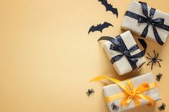 Gift boxes with decorative spiders and bats on orange background Stock Photos