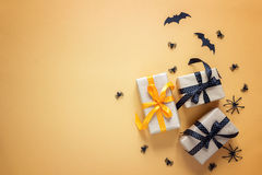 Gift boxes with decorative spiders and bats on orange background Stock Image