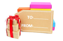 Gift boxes of different sizes and colors and a blank label Royalty Free Stock Image