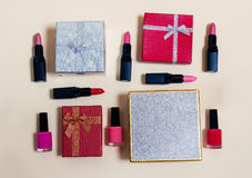 Gift boxes and female decorative cosmetics on beige background Stock Images