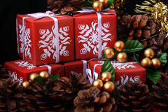 Gift boxes among fir cones as Christmas background Royalty Free Stock Image