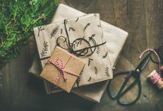 Gift boxes, fur tree branches, rope, scissors over wooden background. Preparing for Christmas or New Year holiday. Flat-lay of gift boxes, green fur tree Stock Photo